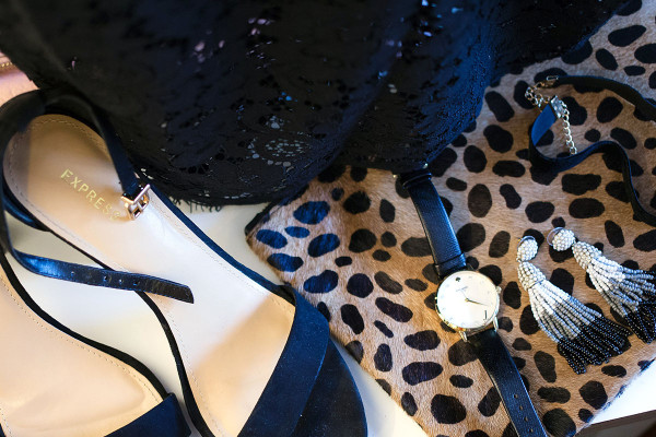 Style blogger Bows & Sequins displays a leopard purse, gold bracelet, gold necklace, gold watch, blue earrings, and more while preparing for a special occasion on New York.