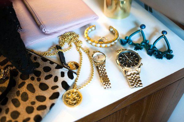 Style blogger Bows & Sequins displays a purse, bracelet, necklace, watch, earrings, and more while preparing for a special occasion on New York.