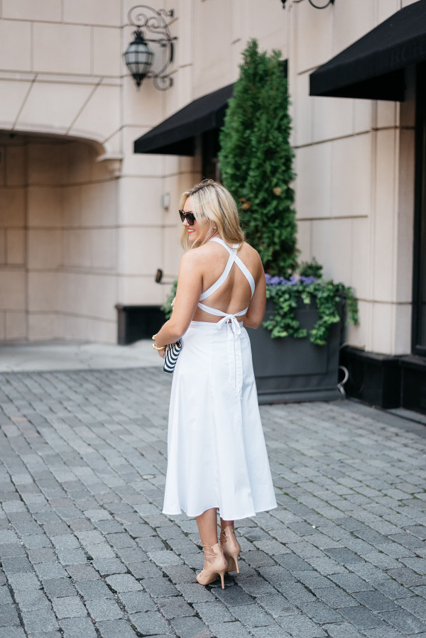 Jessica Sturdy of Bows & Sequins wearing a Fame and Partners white dress, sunglasses, clutch, and heels in Chicago.