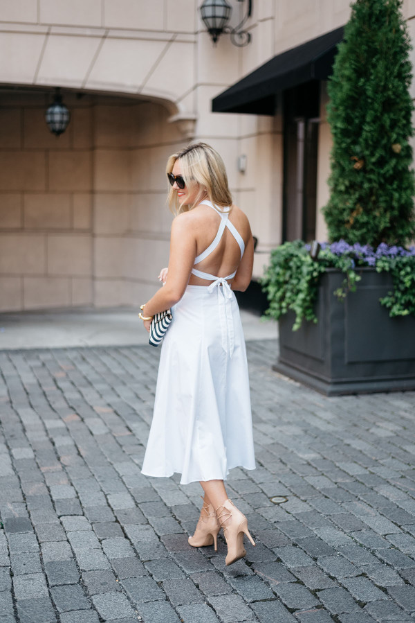 Bows & Sequins wearing a crisscross white dress, sunglasses, and heels in Chicago.