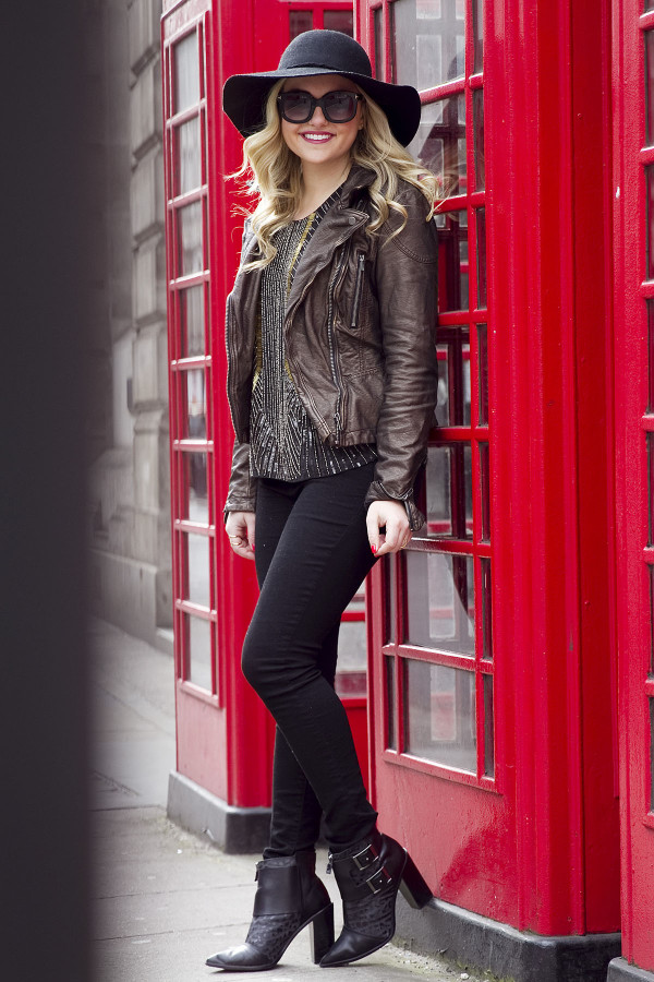 Jessica Sturdy of Bows & Sequins, a fashion-focused lifestyle blog, wearing a black hat, metallic moto jacket, black pants, booties, and sunglasses in London.