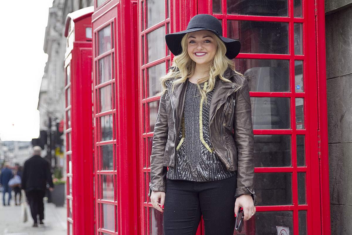 Travel and fashion blogger Jessica Sturdy of Bows & Sequins wearing a black hat, moto jacket, beaded tank, and black pants in London.