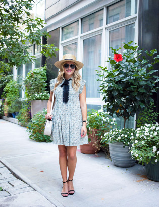 Fashion blogger Jessica Sturdy of Bows & Sequins styling a blue floral dress with a bow, straw hat, sunglasses, and Kate Spade purse in New York City.