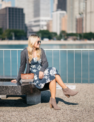 Fashion blogger Bows & Sequins styles a blue navy floral dress, long grey sweater, aviator sunglasses, Sword & Plough clutch purse, and Steve Madden booties in Chicago.