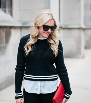 Jessica Sturdy of Bows & Sequins, a fashion-focused lifestyle blog, wearing a black and white sweater, red clutch purse, and sunglasses.