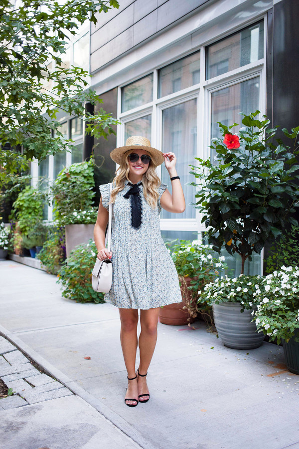 Bows & Sequins styling a floral dress with a bow, straw hat, aviator sunglasses, and Kate Spade purse in NYC.