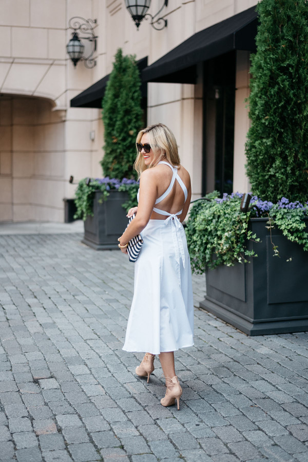 Jessica Sturdy of fashion blog Bows & Sequins wearing a white crisscross dress, heels and sunglasses in Chicago.