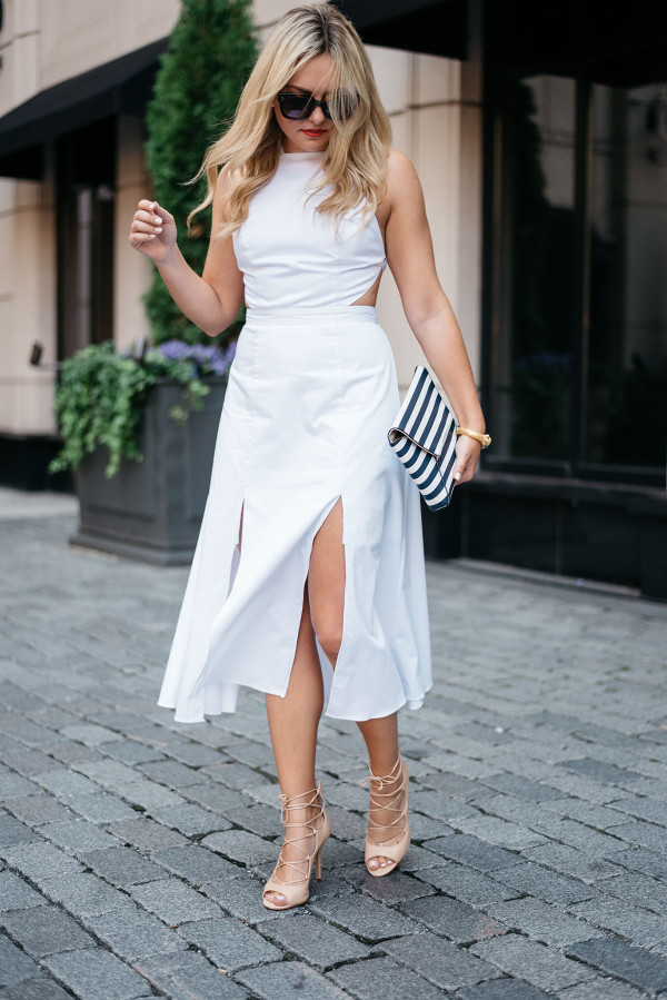 Fashion blogger Bows & Sequins wearing a white dress, black and white striped clutch purse, and Celine sunglasses.