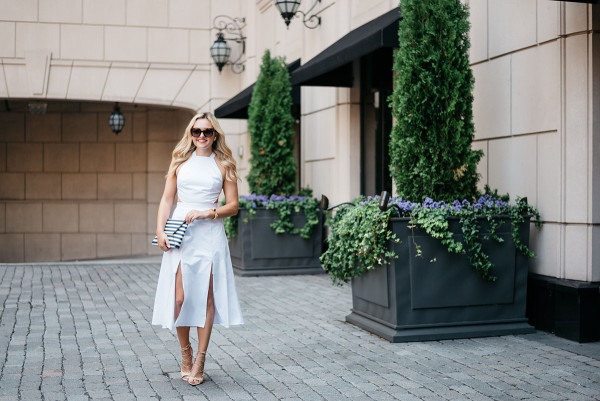 Style blogger Bows & Sequins wearing a white dress, black and white clutch, heels, and sunglasses in Chicago.