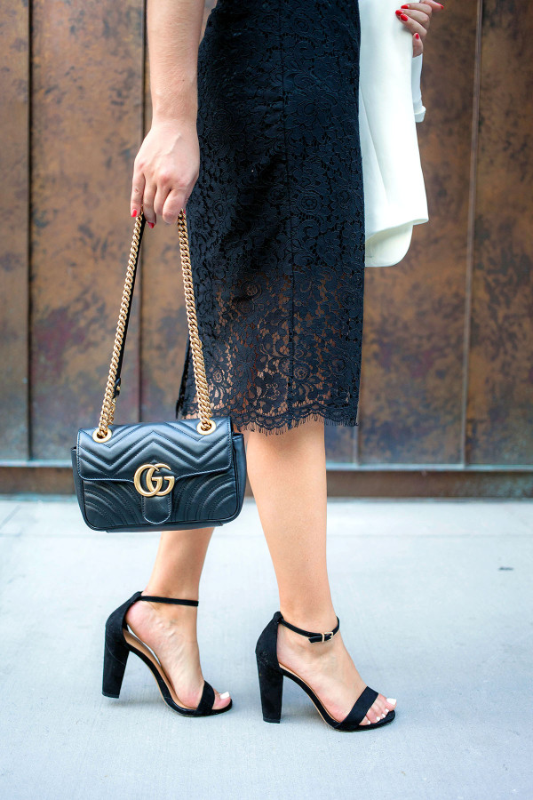 Jessica Sturdy of fashion blog Bows & Sequins styling a Gucci purse with a little black dress and strap sandals in New York.