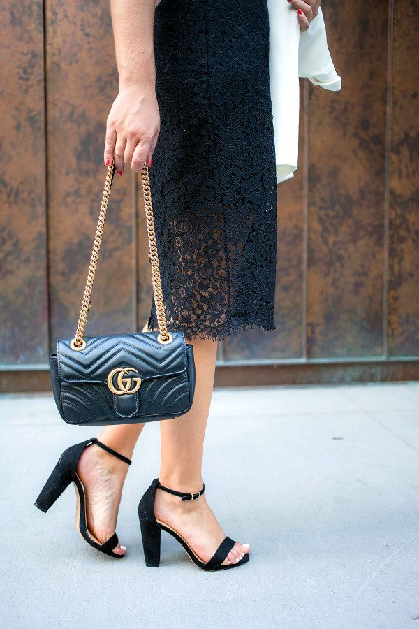 Bows & Sequins, a fashion-focused lifestyle blog, holds a black Gucci purse, black dress, and black heels in New York.