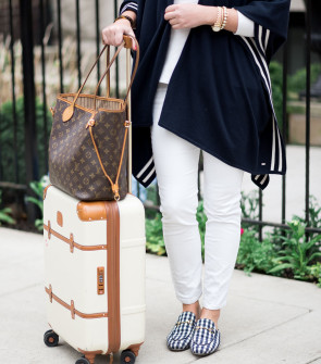 Bows & Sequins wearing a stylish and easy outfit for traveling: navy striped sweater, white corduroy pants, Gucci gingham loafers, Louis Vuitton Neverfull Tote, and Bric's Bellagio cream spinner suitcase. Comfortable, but chic!