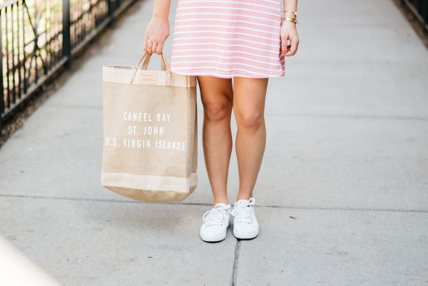 Jessica Sturdy of Bows & Sequins wearing a pink and white striped dress, white eyelet sneakers, and an Apolis Market tote.