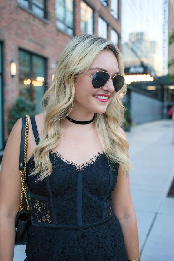 Jessica Sturdy of fashion blog Bows & Sequins wears an Express black dress, black choker, and aviator sunglasses.