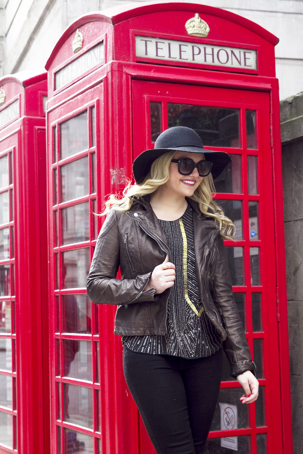 Jessica Sturdy of Bows & Sequins, a fashion-focused lifestyle and travel blog, wearing a black hat, metallic moto jacket, black pants, and sunglasses in front of a phone booth in London.
