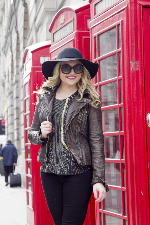 Travel and fashion blogger Bows & Sequins wearing a black hat, sunglasses, and moto jacket in front of a phone booth in London.