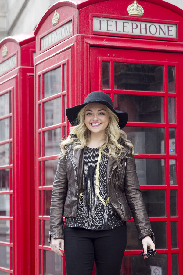 Jessica Sturdy of Bows & Sequins, a fashion-focused lifestyle and travel blog, styling a moto jacket, black hat, and a beaded tank in front of a phone booth in London.