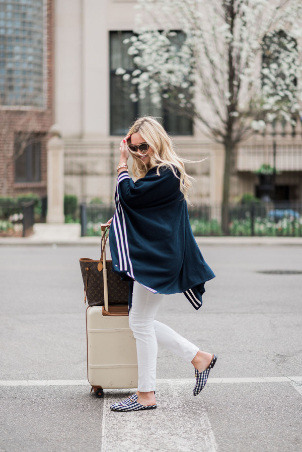 Bows & Sequins wearing a stylish and easy outfit for traveling: navy striped sweater, white corduroy pants, Gucci gingham loafers, Louis Vuitton Neverfull Tote, Bric's Bellagio cream spinner suitcase, and Tom Ford sunglasses. Comfortable, but chic!