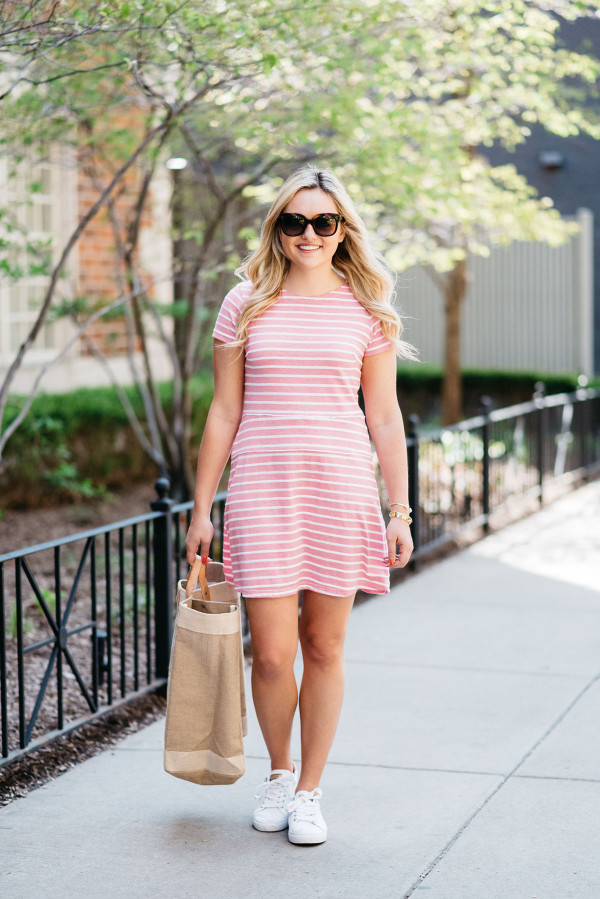 Jessica Sturdy of Bows & Sequins wearing a Sail to Sable pink and white striped dress, Celine sunglasses, and a tan tote.