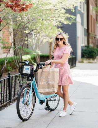 Fashion blogger Bows & Sequins riding a blue Divvy bike in Chicago while wearing a pink and white striped dress and white sneakers.