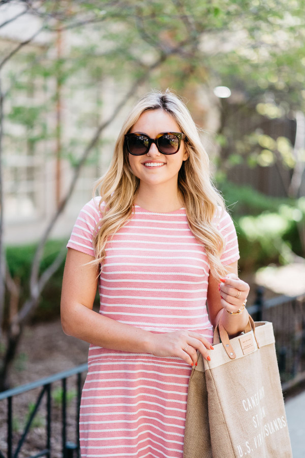 Fashion blogger Bows & Sequins wearing a Sail to Sable pink and white striped dress, Celine sunglasses, and a tan tote.