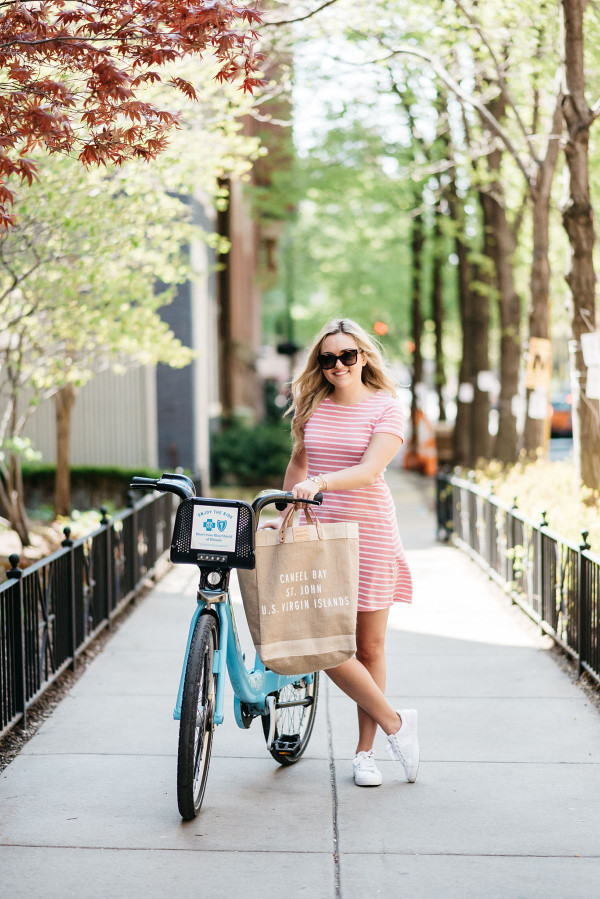 Fashion blogger Bows & Sequins poses with a blue Divvy bike in Chicago while wearing a pink and white striped dress, sunglasses, white sneakers and a tan tote.