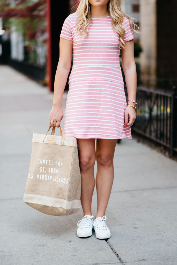 Bows & Sequins, fashion-focused lifestyle blogger, wearing a pink and white striped dress, white Tommy Hilfiger eyelet sneakers, a Apolis Market tote, and sunglasses.