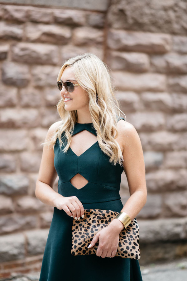 Jessica Sturdy of Bows & Sequins, a fashion blog, wearing a green cutout dress, sunglasses, and leopard clutch purse in Chicago.