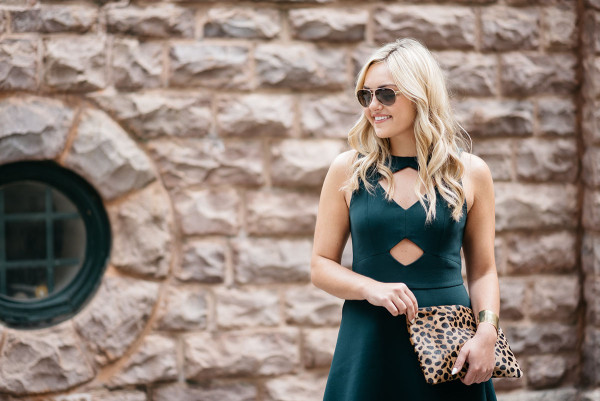 Style blogger Bows & Sequins wearing a green cutout dress, sunglasses, and leopard clutch purse in Chicago.