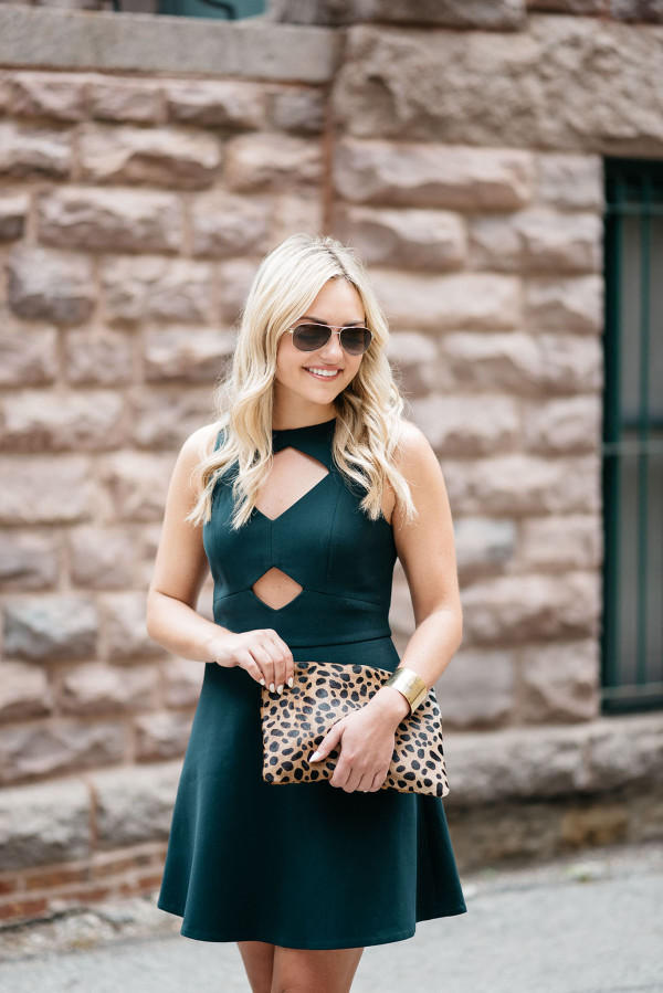 Fashion blogger Bows & Sequins styling a green Rachel Zoe cutout dress, sunglasses, and leopard clutch in Chicago.