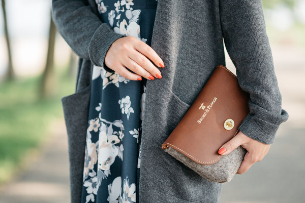 Jessica Sturdy of Bows & Sequins wearing a navy floral dress, grey sweater, and tan and grey wool clutch.