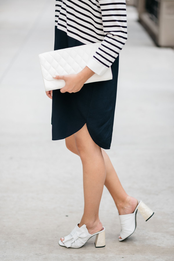 Fashion blogger Bows & Sequins styling a striped t-shirt dress, white bow shoes, and a white clutch purse.
