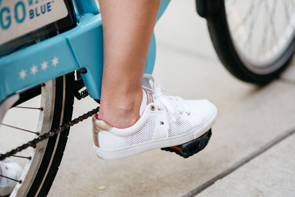 Fashion blogger Bows & Sequins rides a blue Divvy bike in Chicago while wearing white Tommy Hilfiger eyelet sneakers.
