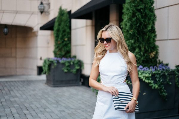 Fashion blogger Bows & Sequins wearing a white dress, black and white striped clutch purse, and sunglasses.