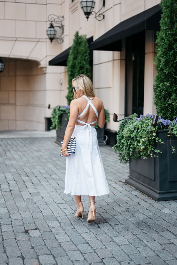 Fashion blogger Bows & Sequins styling a white dress with a cross cross back, black and white clutch purse, and heels in Chicago.