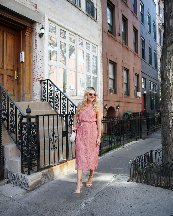 Fashion blogger Bows & Sequins wearing a pink lace midi dress during New York Fashion Week. Jessica styled the outfit with nude lace-up sandals, a Kate Spade crossbody bag, and blush pink square cat-eye sunglasses.
