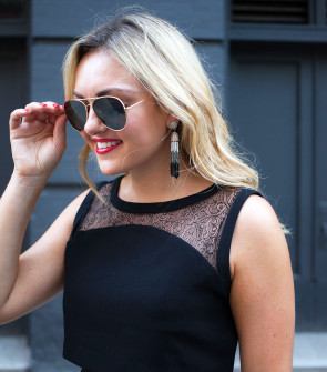 Bows & Sequins styling a black lace dress with BaubleBar Pinata tassel earrings.