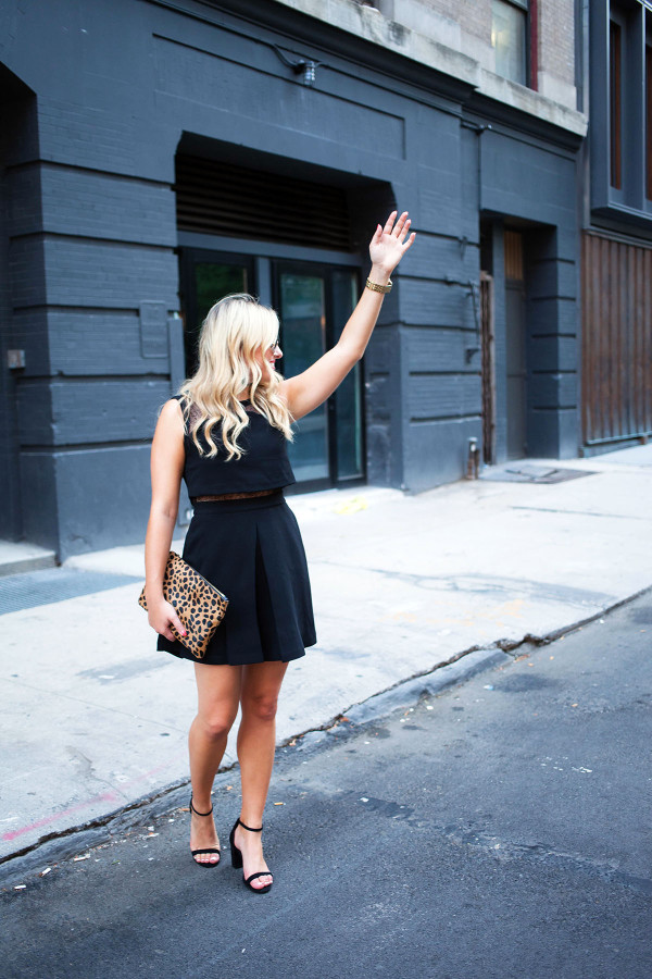 Fashion blogger Bows & Sequins wearing a little black dress, ankle strap sandals, and a leopard clutch in New York City.