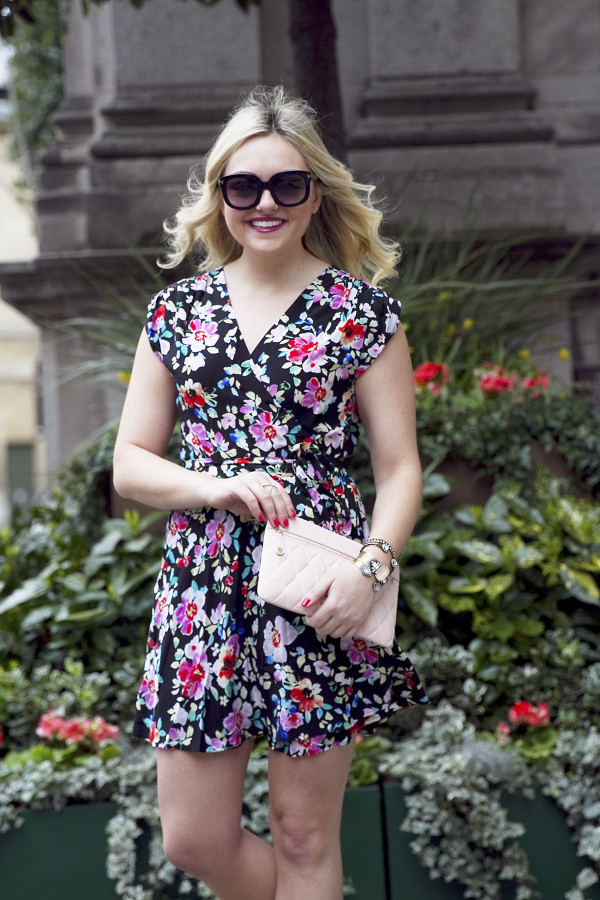 Travel and fashion blogger Bows & Sequins styling a navy floral wrap dress, sunglasses, and a blush leather clutch purse in London.