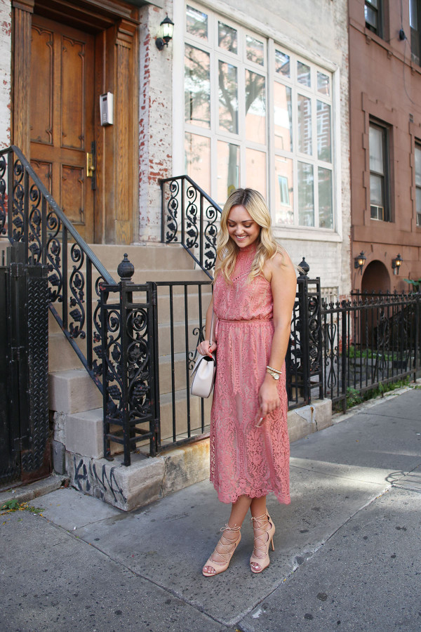 Fashion blogger Bows & Sequins wearing a pink lace midi dress during New York Fashion Week. Jessica styled the outfit with nude lace-up sandals, a Kate Spade crossbody bag, and blush pink square cat-eye sunglasses. Makeup was done by Mary Kay via GlamSquad!