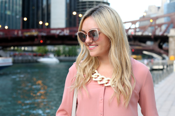 Bows & Sequins wearing blush pink sunglasses, a rosy button-front blouse, and a white link necklace.