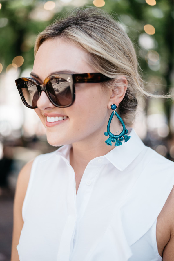 Travel blogger Bows & Sequins wearing teal tassel Bauble Bar earrings and Celine sunglasses in Mariano Park in Chicago.