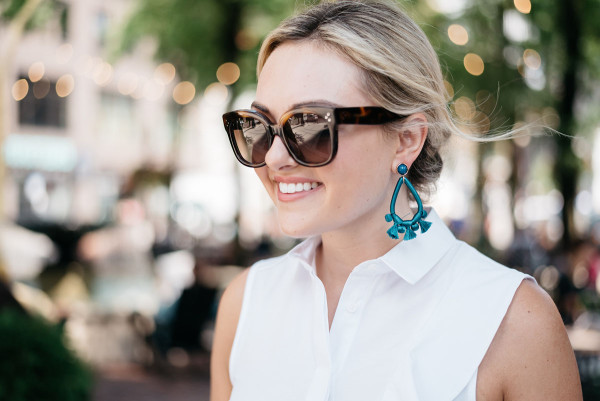 Style blogger Bows & Sequins wearing Celine tortoise sunglasses, blue tassel earrings from BaubleBar, and a white sleeveless collared shirt.