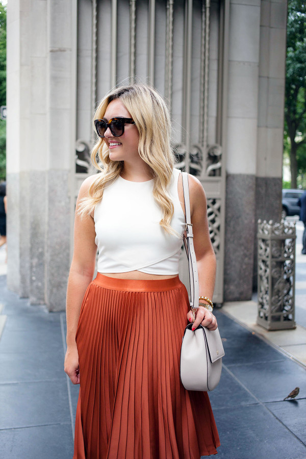 Blogger Bows & Sequins styling a crop top in a sophisticated way. She paired it with a pleated skirt, Celine sunglasses, and a Kate Spade crossbody saddle bag.