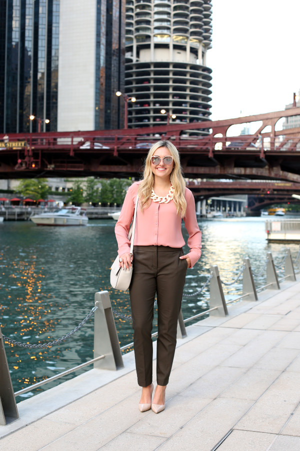 Bows & Sequins wearing a cute fall work outfit. She paired a silky pink blouse with olive green slim-fit ankle trousers, nude pointed toe pumps, a cream-colored crossbody bag, a white link statement necklace, and blush pink sunglasses.