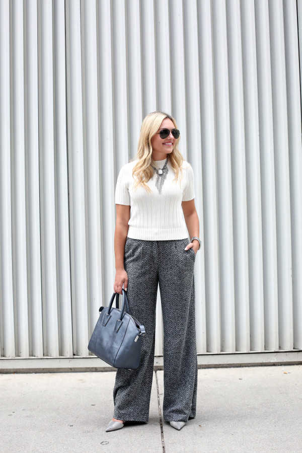 Bows & Sequins styling a pair of chevron herringbone wool wide-leg pants for the work place. Jessica styled them with a short sleeved sweater, a statement necklace, a metallic tote, and textured grey pumps.