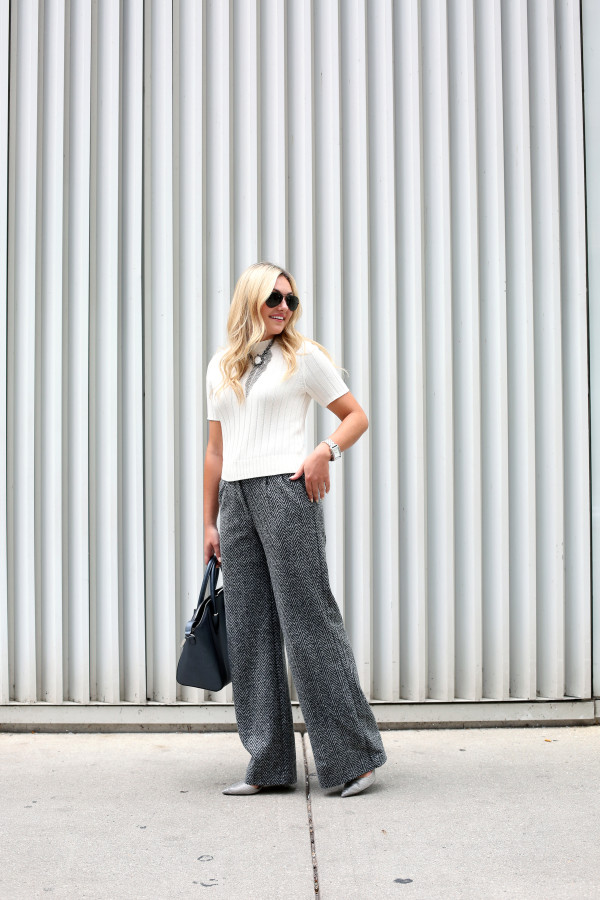 Bows & Sequins wearing a pair of chevron herringbone wool wide-leg pants for the work place. Jessica styled them with a short sleeved sweater, a statement necklace, a metallic tote, and textured grey pumps.