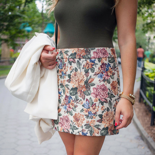 Bows & Sequins wearing an olive green body suit, a floral mini skirt, and a white blazer for a cute, fall transition outfit!