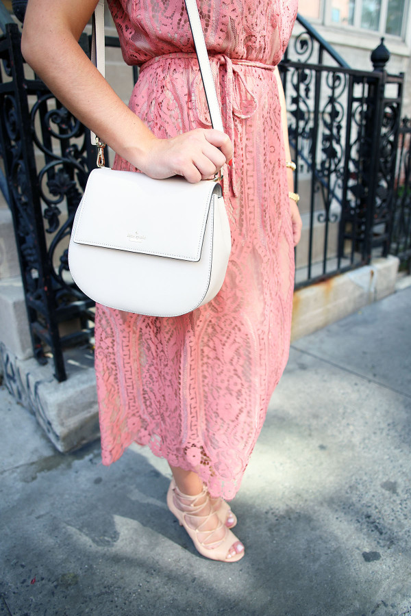 Blogger Bows & Sequins styling a Wayf pink lace midi dress, a Kate Spade Byrdie crossbody bag, and Vince Camuto nude lace-up heels during NYFW.