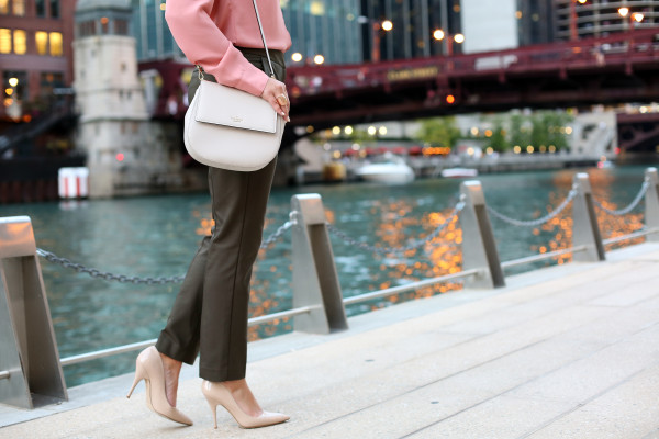 Bows & Sequins styling a pair of olive green pants for work. She paired the ankle-length pants with a rosy pink silky blouse, nude pointed toe pumps from Kate Spade, and a cream-colored crossbody bag.